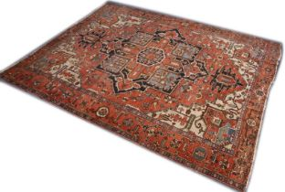 A GOOD LARGE PERSIAN HERIZ CARPET, red ground with central medallion and stylised decoration. 13ft