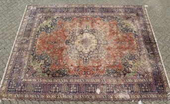 A LARGE PERSIAN CARPET, rust ground central panel, with all over stylised flora decoration ( some