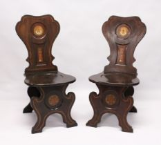 A GOOD PAIR OF REGENCY MAHOGANY HALL CHAIRS with shaped backs with painted crest, solid seats