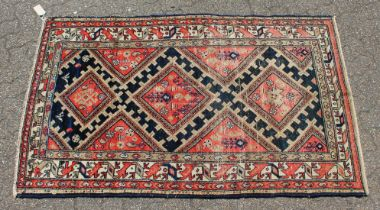 A MID 20TH CENTURY MALAYER RUG, bright red ground with three central lozenges. 6ft 5ins x 3ft