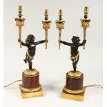 AS VERY GOOD PAIR OF REGENCY BRONZE AND ORMOLU TWO BRANCHED CHERUB CANDLESTICK each holding