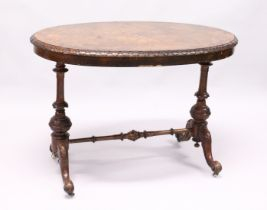 A VICTOTIAN FIGURED WALNUT OVAL STRETCHER TABLE with quartered top carved edges on turned legs