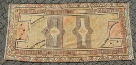 AN UNUSUAL KHOTAN (CAUCASIAN) CARPET, beige ground, two central lozenge shaped medallions with