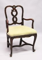 A SMALL GEORGE II DESIGN MAHOGANY OPEN ARMCHAIR with curved cresting, wavy splats, shepherd's