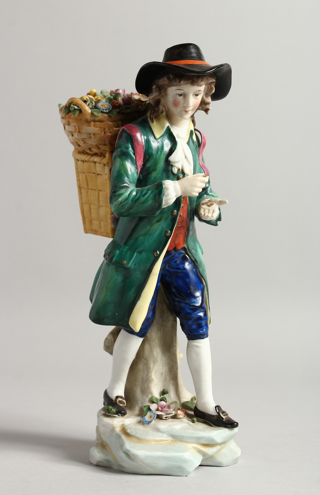 A SAMSON CHELSEA DERRY PORCELAIN FIGURE of a man, a basket of flowers on his back 9ins high.