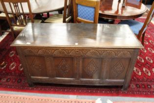 A LARGE 18TH CENTURY OAK COFFER with plain top, four carved panels to the front. 4ft 6ins wide.