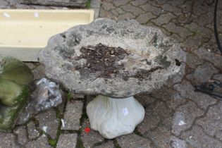 A shell shaped reconstituted stone bird bath.