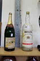A large bottle of old champagne and a Bell's whisky bottle (no contents).