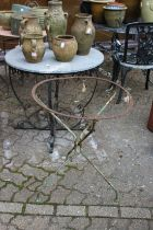 Two wrought iron table bases, one with a circular reconstituted stone top.