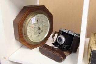 A folding camera and a barometer.