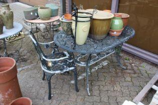 A painted cast aluminium patio table and an armchair.