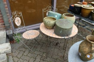 A modern wrought iron circular patio table and a pair of matching folding chairs.