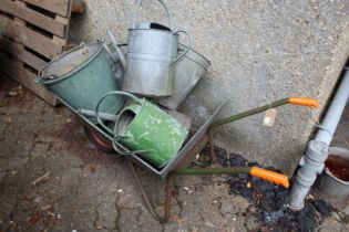 A wheelbarrow and a quantity of galvanized watering cans and buckets.