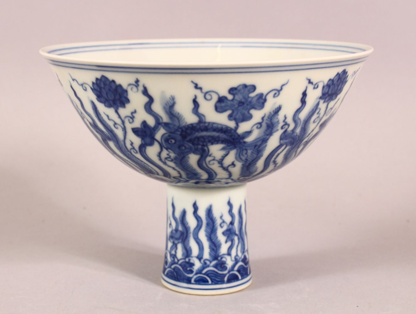 A CHINESE BLUE AND WHITE PORCELAIN STEM CUP, the bowl painted with fish amongst aquatic flora