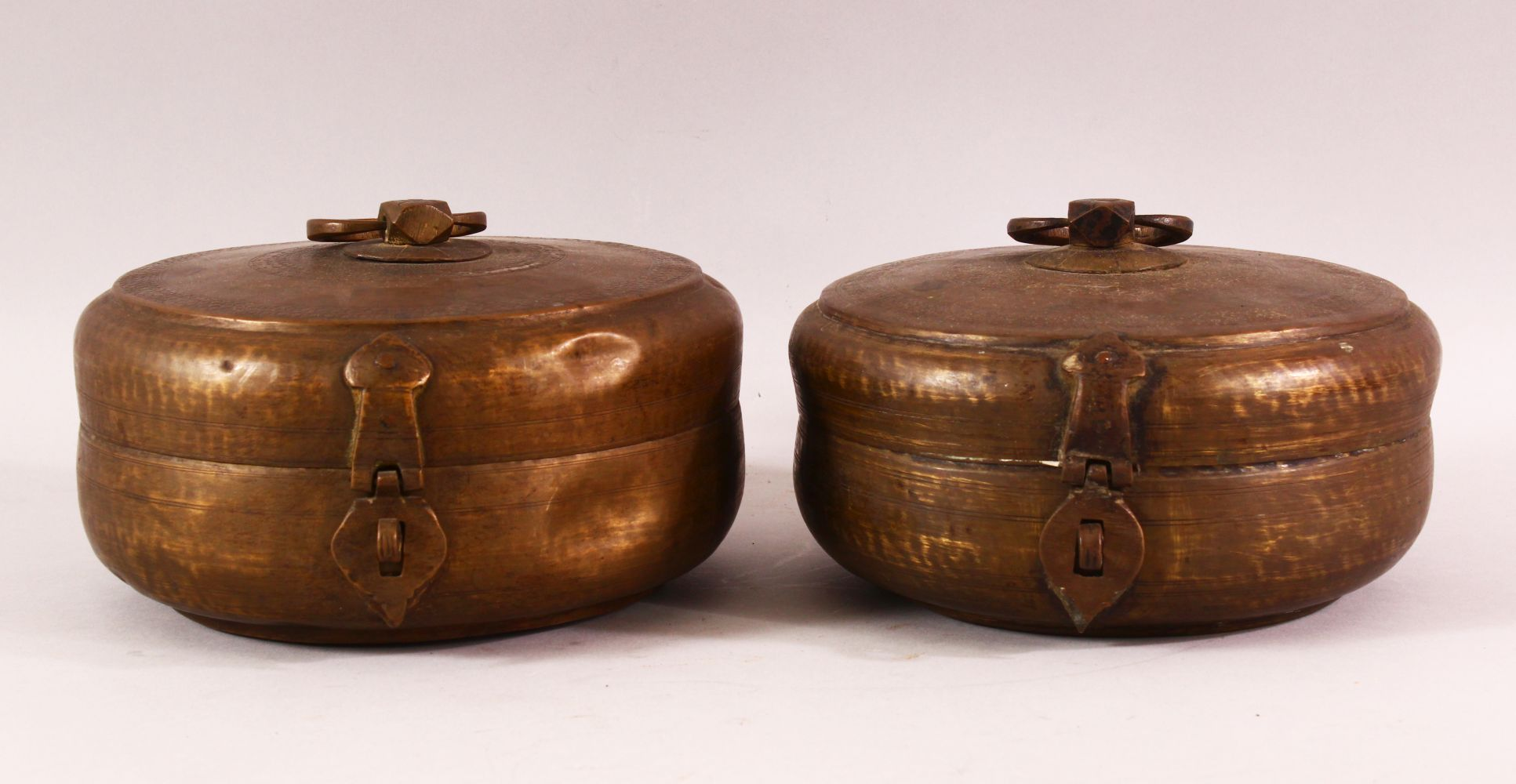 A PAIR OF INDIAN SPICE BOXES, both with hinged lid and handle to top, both approx. 21cm diameter.