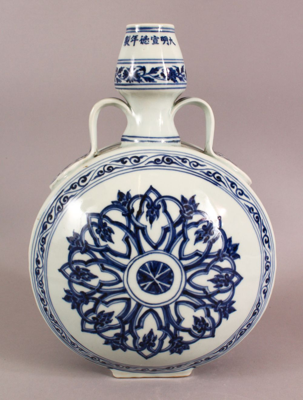 A CHINESE BLUE AND WHITE TWIN HANDLED PORCELAIN MOON FLASK, painted with stylised motifs, six