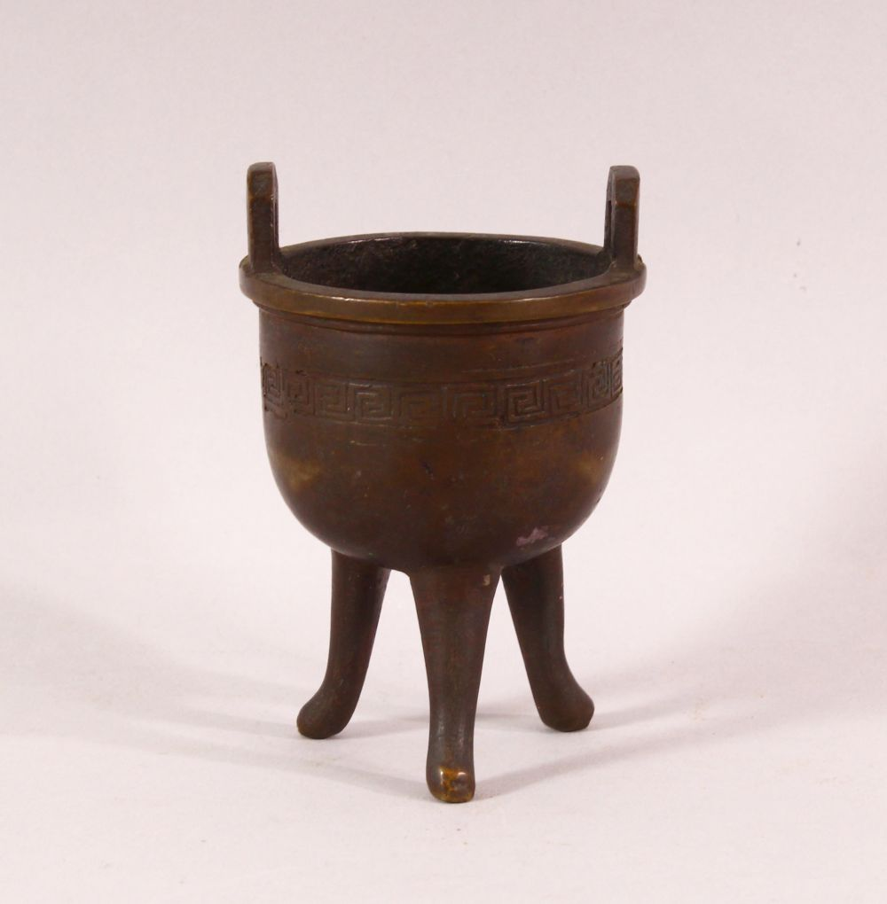 A SMALL 19TH CENTURY CHINESE TWIN HANDLE TRIPOD CENSER, the body with greek key decoration, 9.5cm