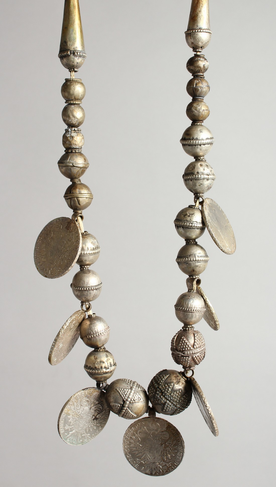 AN ISLAMIC SILVER NECKLACE with seven coins.