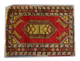 A SMALL PERSIAN/TURKISH RUG, red ground with central lozenge shape design (central join) 3ft 10ins x