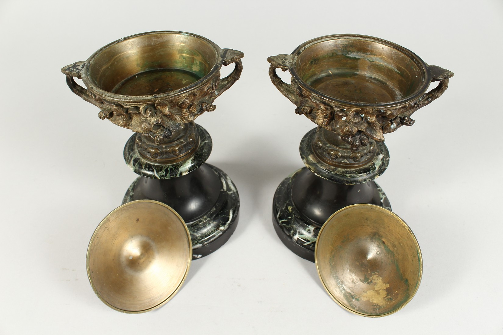 A PAIR OF BRONZE TWO HANDLED URNS AND COVERS on circular marble bases. 10ins high. - Image 4 of 6