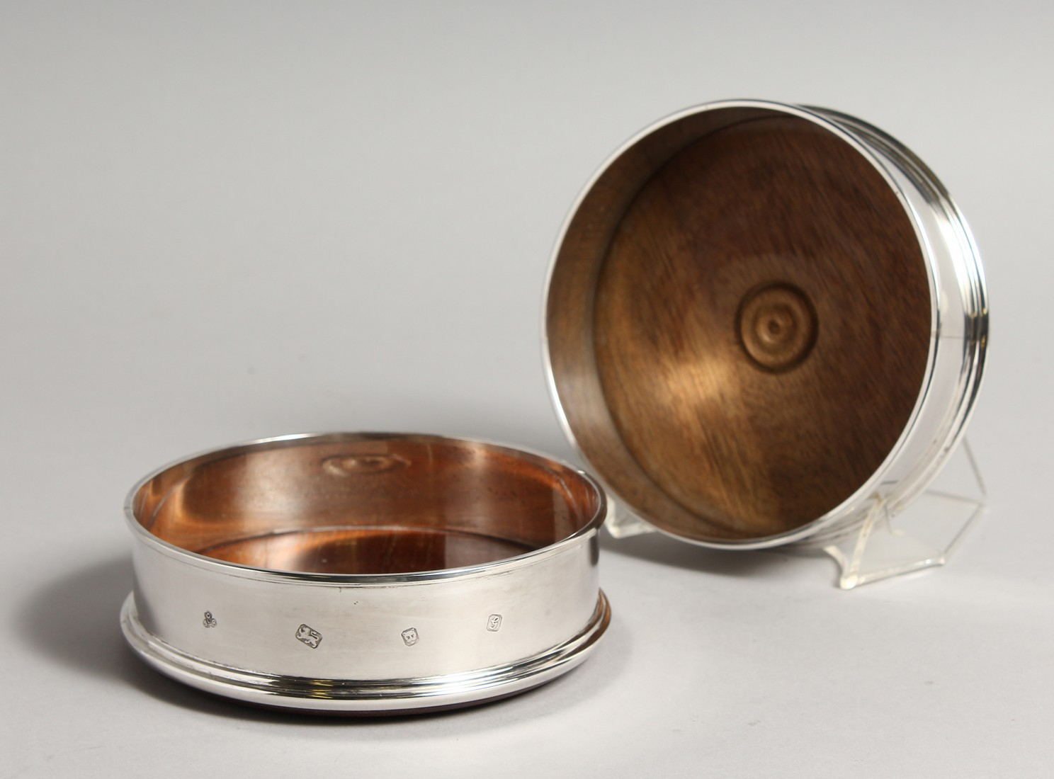 A PAIR OF MODERN PLAIN SILVER WINE WINE COASTERS wit turned wood bases 4.75diameter London 2003