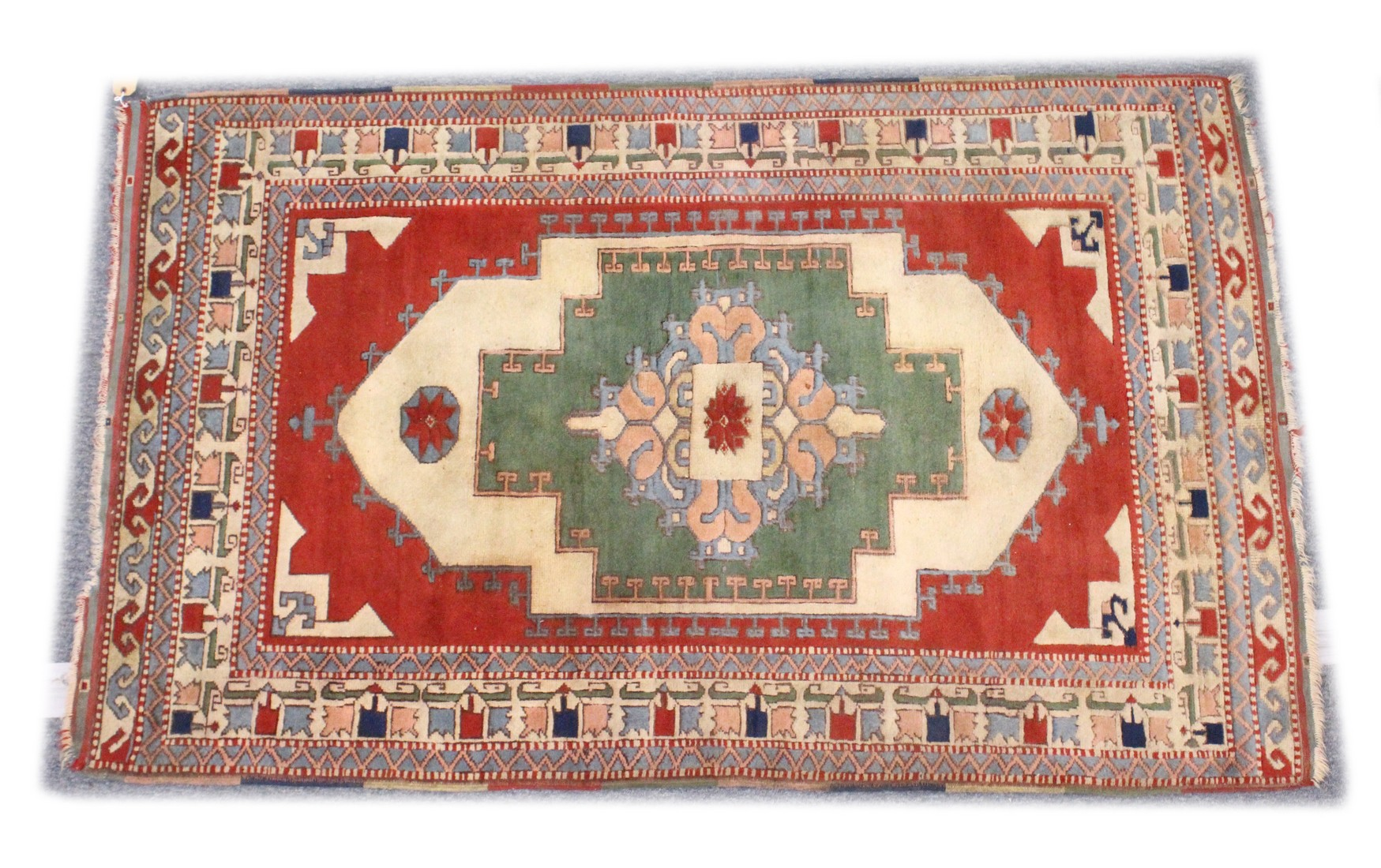 A TURKISH WOVEN WOOL RUG, early 20th Century with a central pale green ground panel and stylised