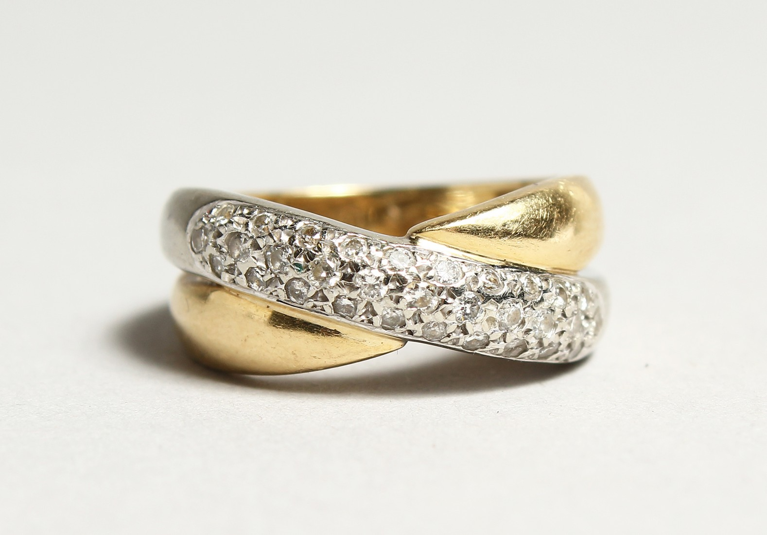 AN 18CT GOLD DIAMOND SET CROSS OVER RING