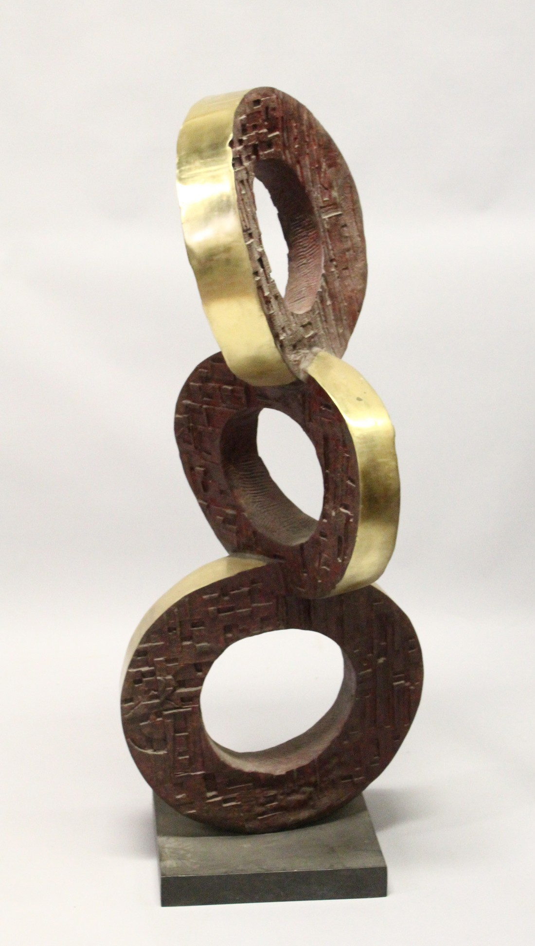 A LARGE POLISHED AND PATTINATED BRONZE ABSTRACT GROUP OF THREE CONJOINED CIRCLES, on a square base.