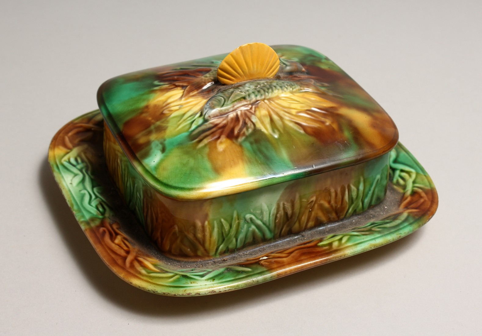 A MAJOLICA SARDINE DISH AND COVER, green and brown glaze with moulded decoration and shell handle.