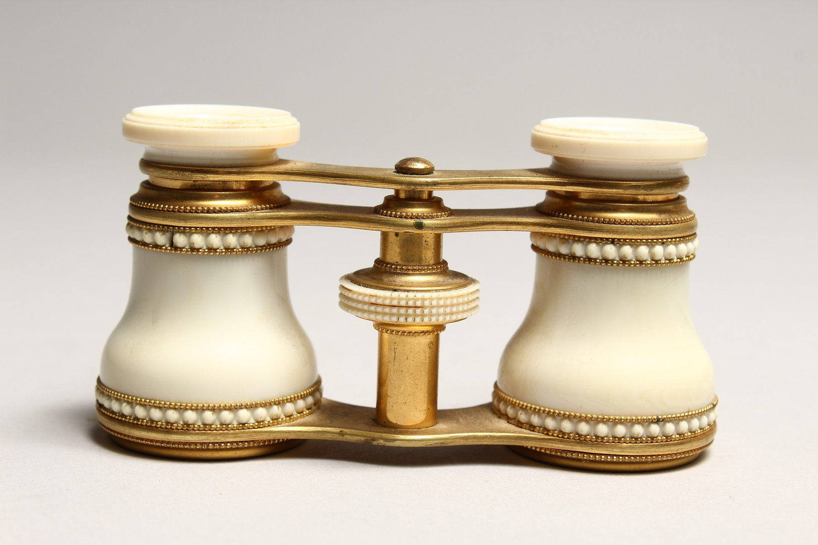 A PAIR OF IVORY AND GILT OPERA GLASSES 4.6ins long.
