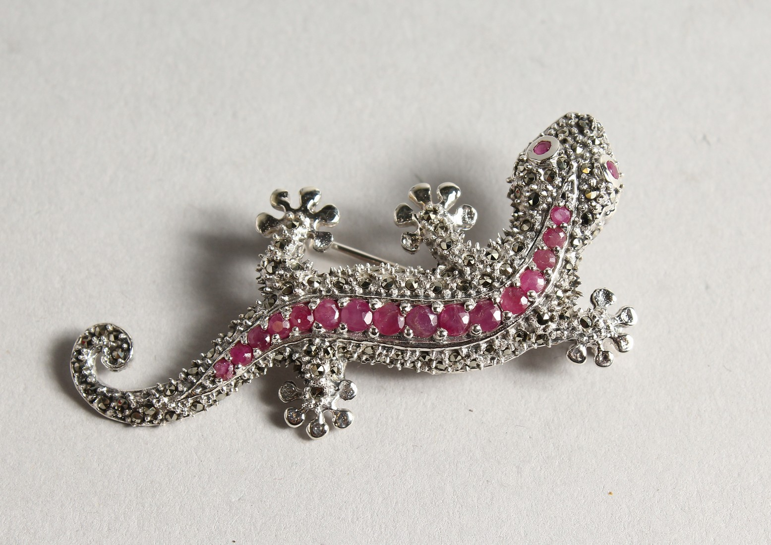 A SILVER MARCASITE AND RUBY LIZARD BROOCH.
