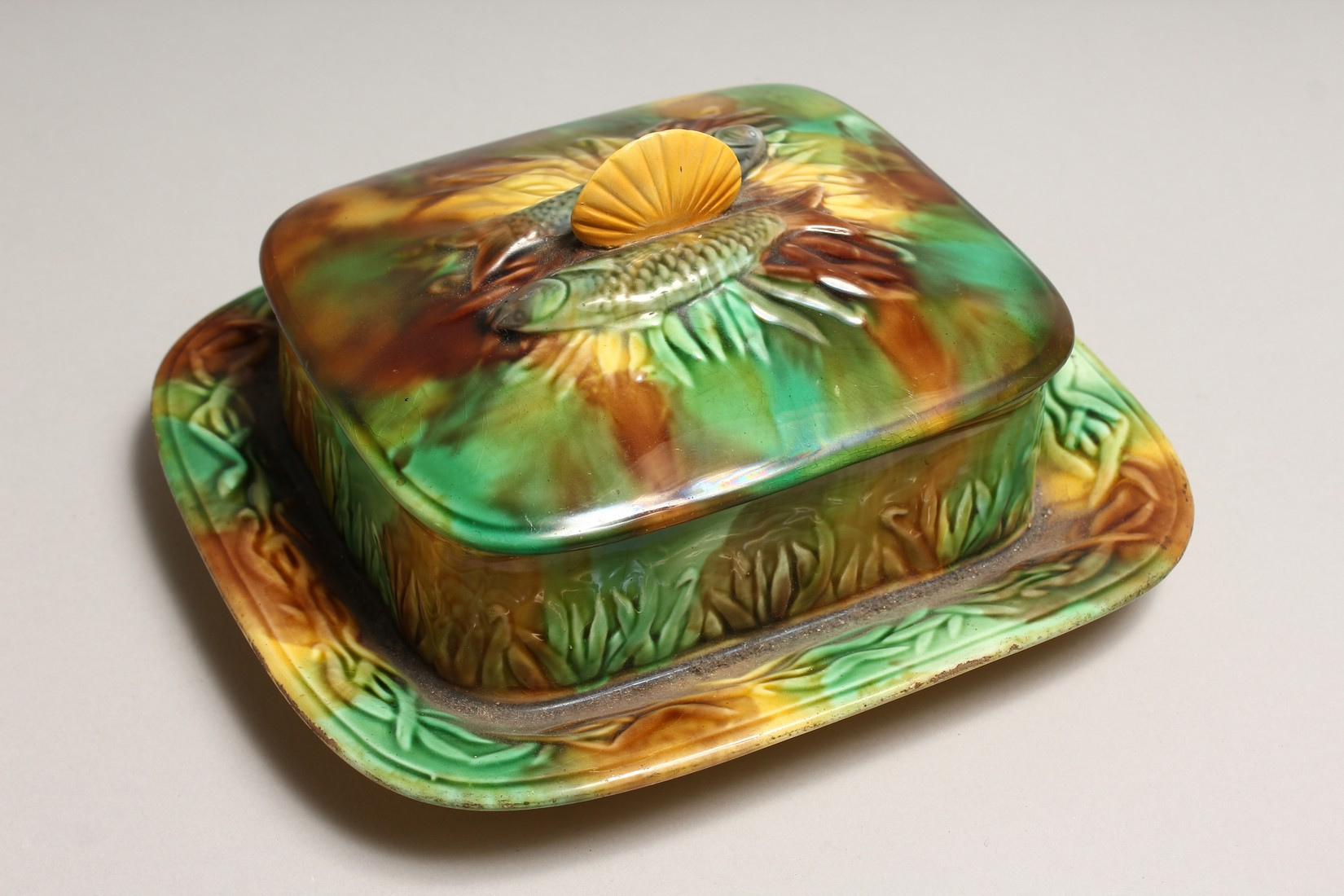 A MAJOLICA SARDINE DISH AND COVER, green and brown glaze with moulded decoration and shell handle. - Image 2 of 4