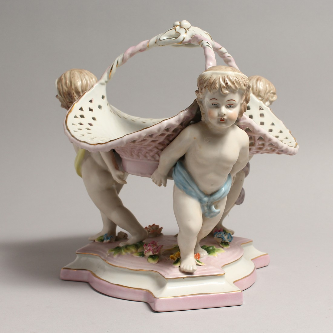 A MEISSEN STYLE PORCELAIN BASKET supported by three cupids. 10ins high