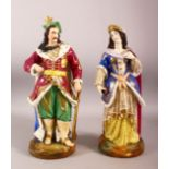 A PAIR OF TURKISH PORCELAIN SULTAN & SULTANA - both in traditional gowns holding objects, 38cm