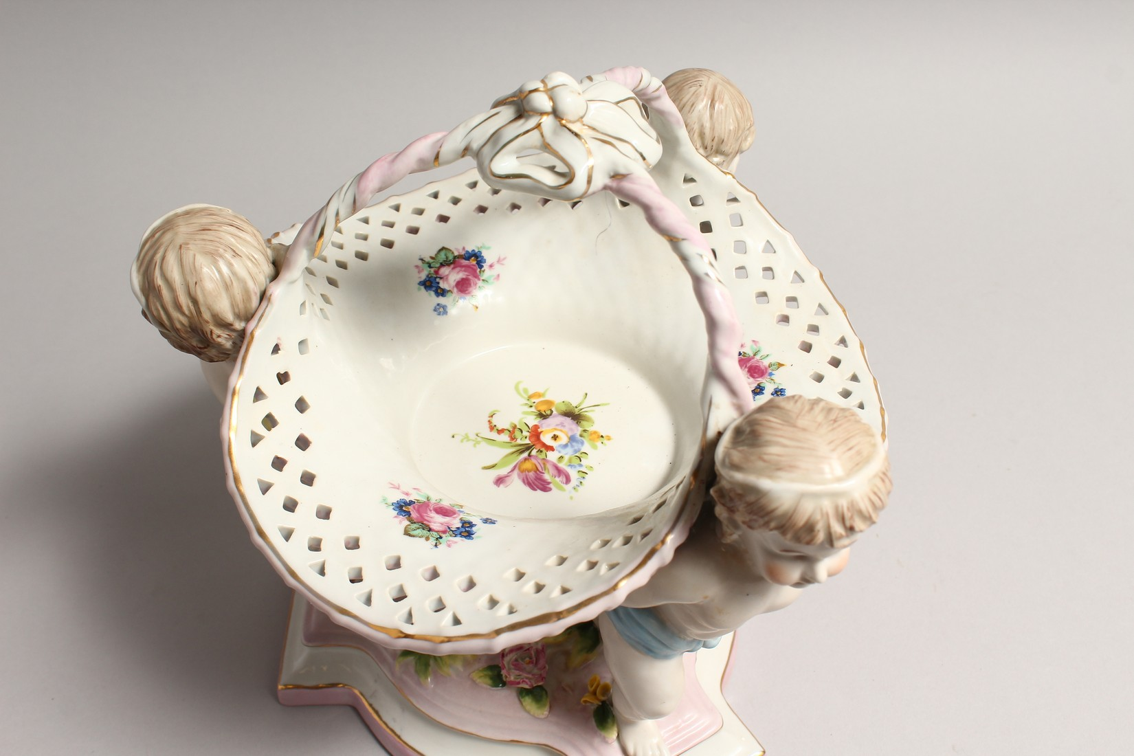 A MEISSEN STYLE PORCELAIN BASKET supported by three cupids. 10ins high - Image 2 of 5