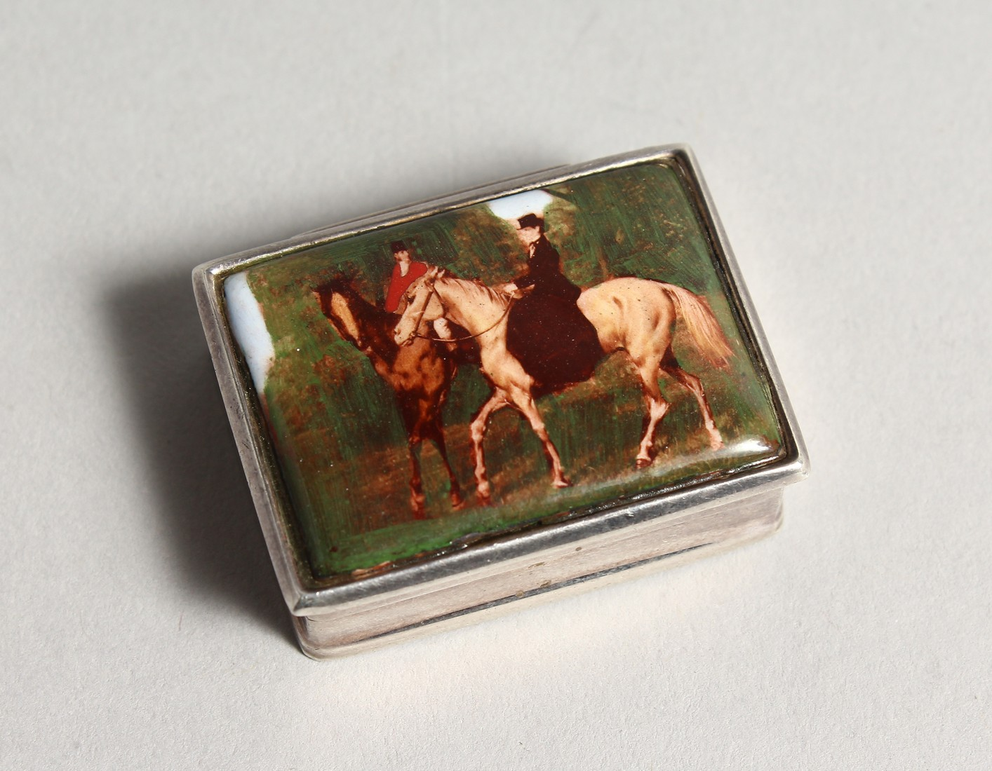 A SILVER AND ENAMEL SNUFF BOX, the lid decorated with figures on horseback. 1.5ins wide