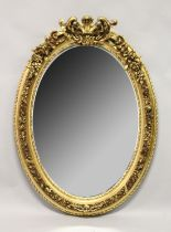 A LARGE DECORATIVE OVAL GILT FRAMED WALL MIRROR. 4ft 2ins high x 3ft wide.