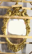 A LARGE IMPRESSIVE GILT FRAMED OVAL MIRROR, the frame mounted with a cherub seated on an urn, with