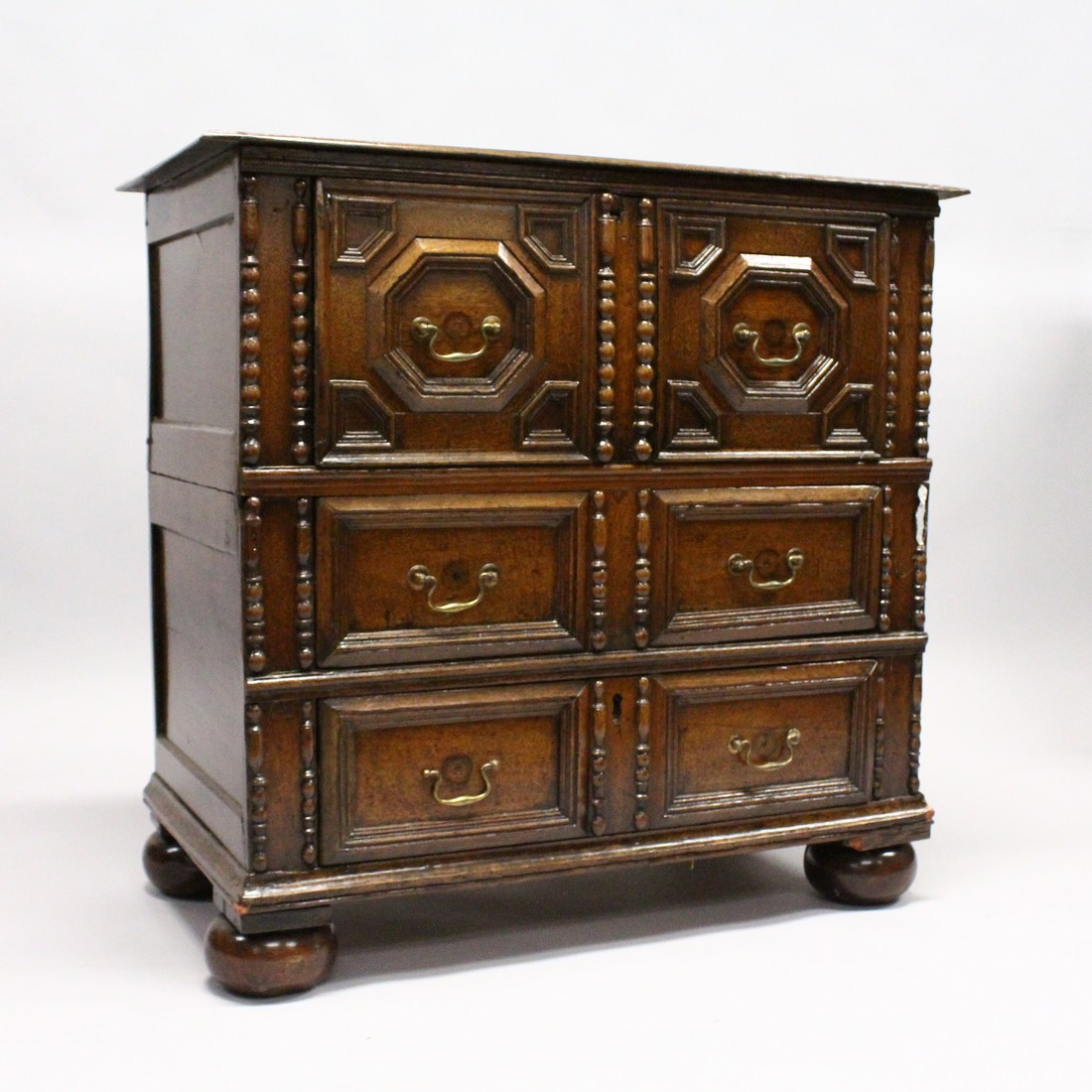 A GOOD LATE 17TH CENTURY LIGHT OAK TWO PIECE LINEN FOLD FRONT CHEST OF THREE DRAWERS, with