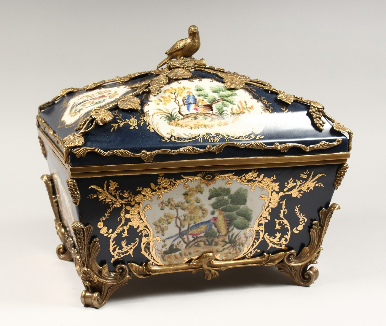 A DECORATIVE PORCELAIN AND ORMOLU MOUNTED SEVRES STYLE CASKET AND COVER. 15ins long