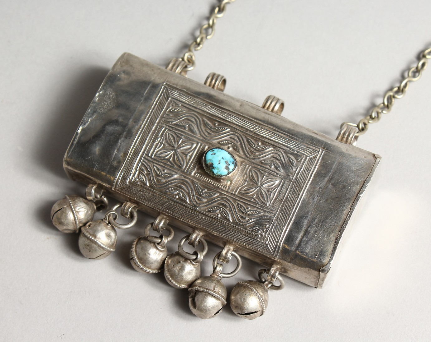 AN ISLAMIC SILVER BOX with bells, stone and chain