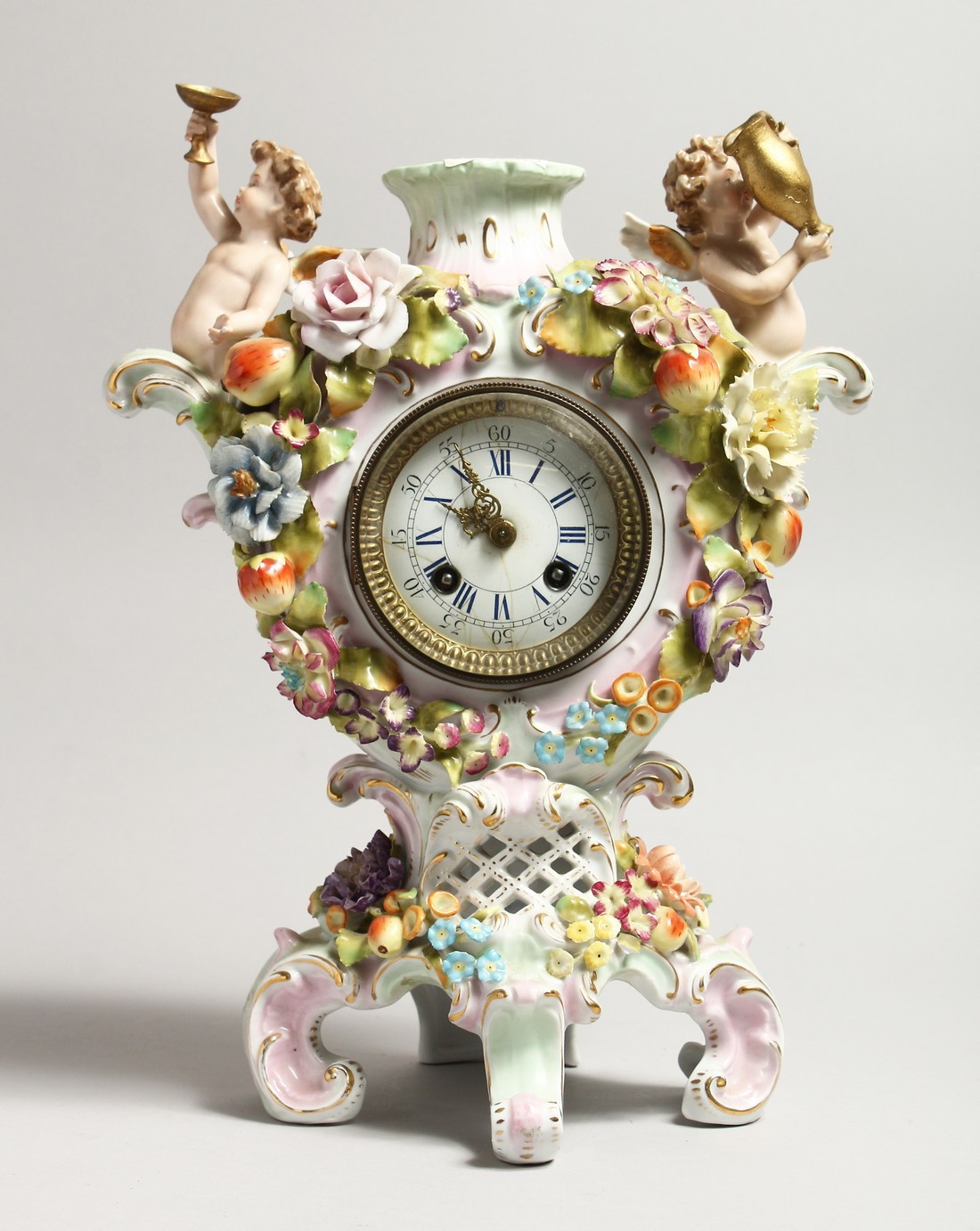 A CONTINENTAL PORCELAIN CUPID AND FLOWER ENCRUSTED CLOCK, with blue and white Roman numerals.