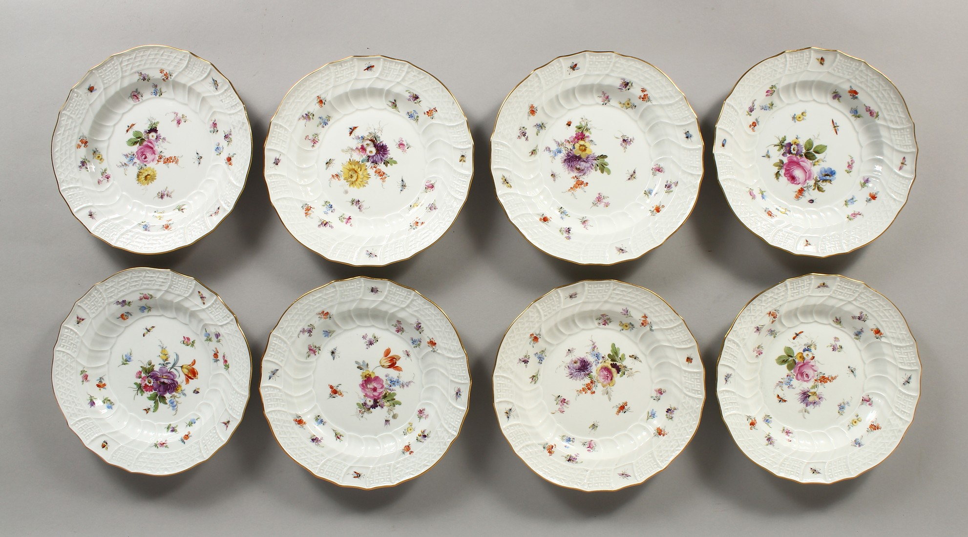 A SET OF EIGHT MEISSEN PORCELAIN DISHES with moulded gilt edged rim, each painted with flowers and