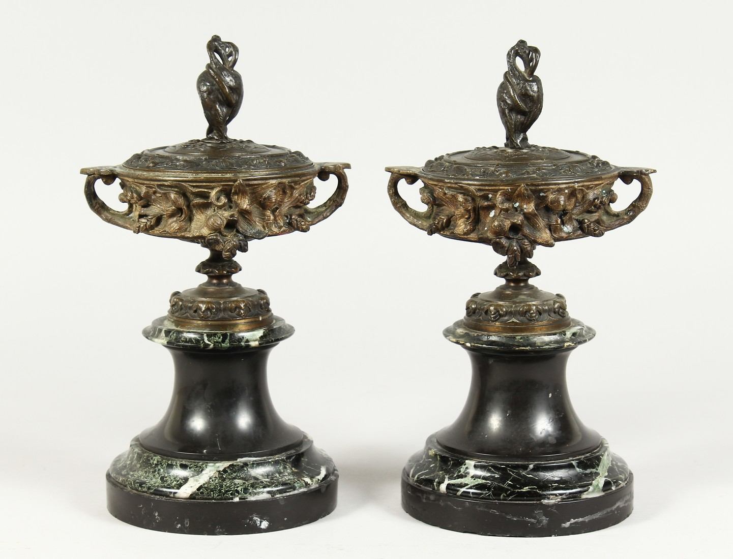 A PAIR OF BRONZE TWO HANDLED URNS AND COVERS on circular marble bases. 10ins high.