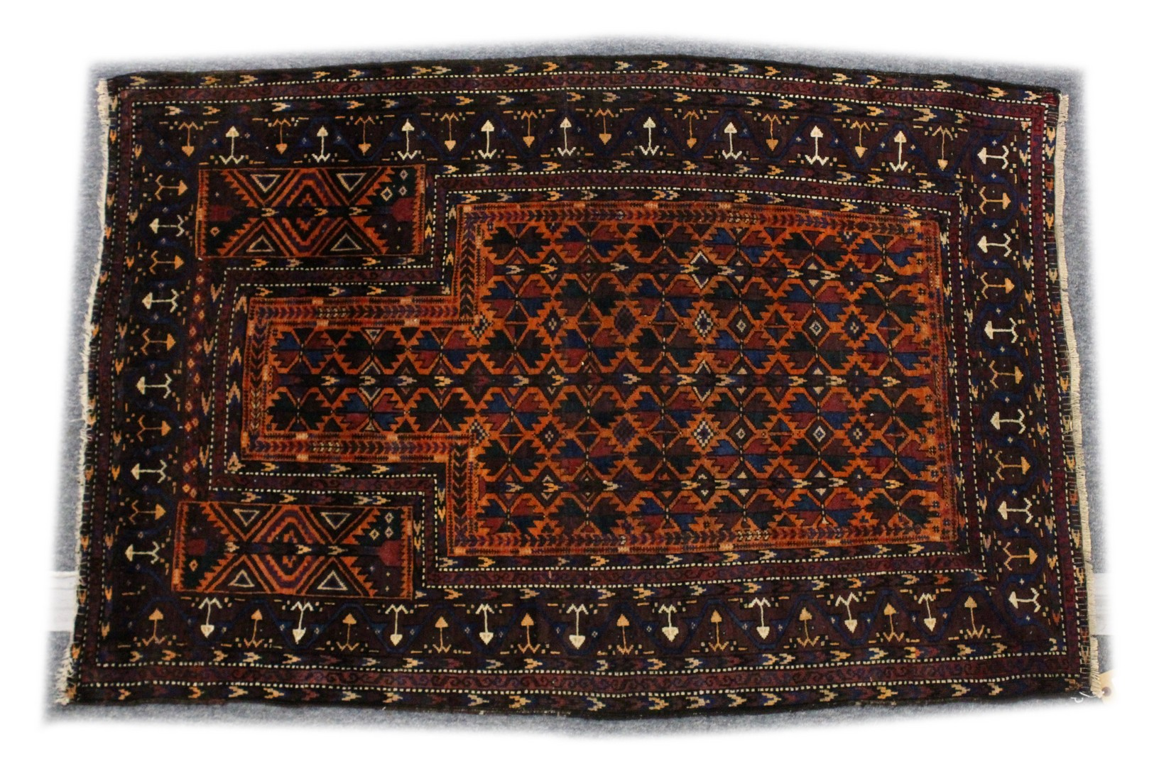 A BELUCHI PRAYER RUG, rust ground with stylised geometric design 5ft x 3ft 5ins