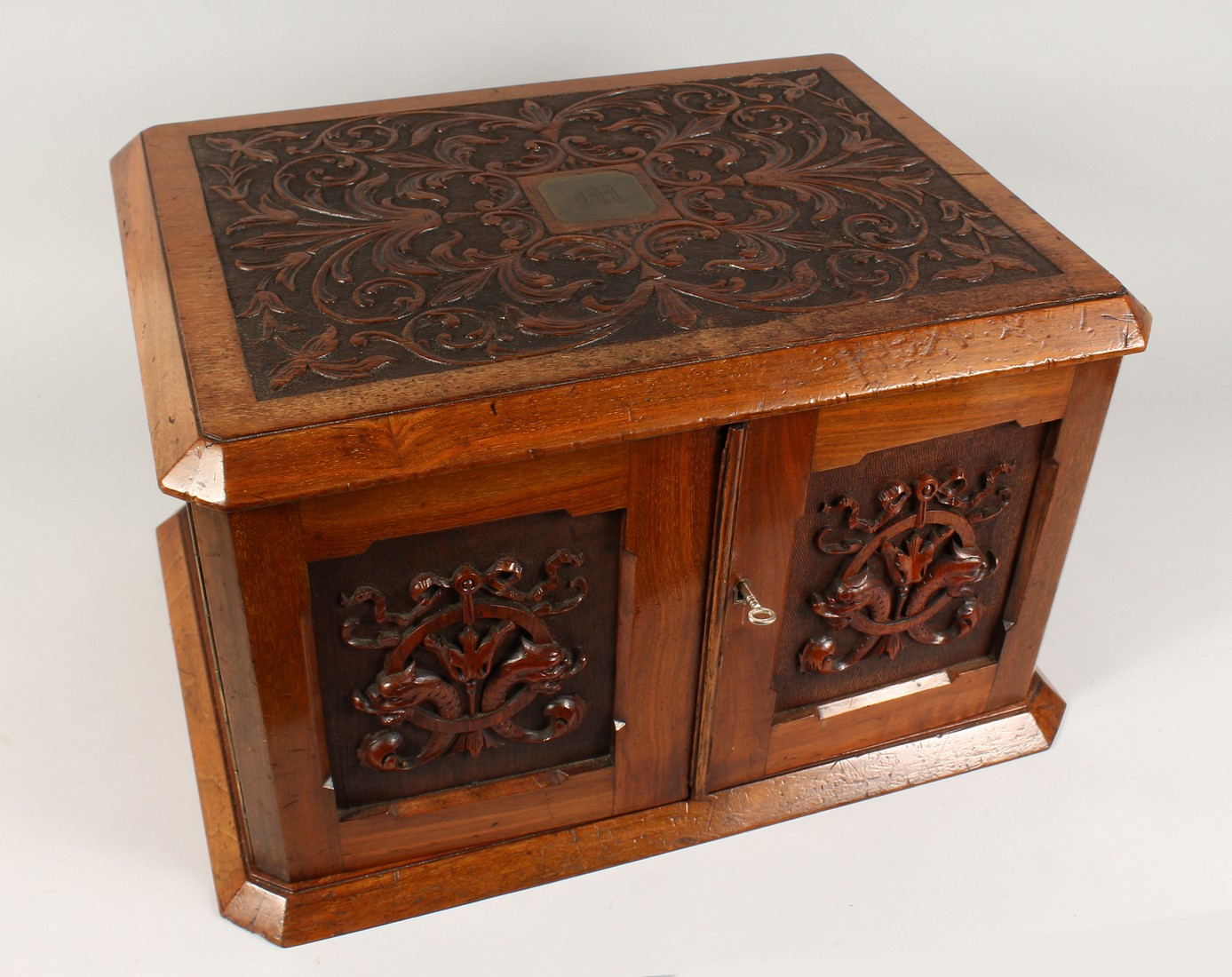 A GOOD VICTORIAN CARVED OVAL TABLE TOP CABINET, the top and doors with carved decoration, the