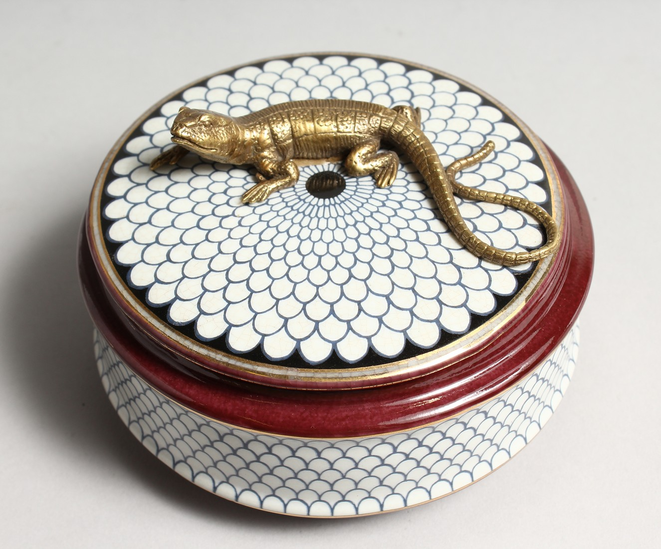 A CIRCULALR PORCELAIN BOX AND COVER with bronze lizard 5ins diameter