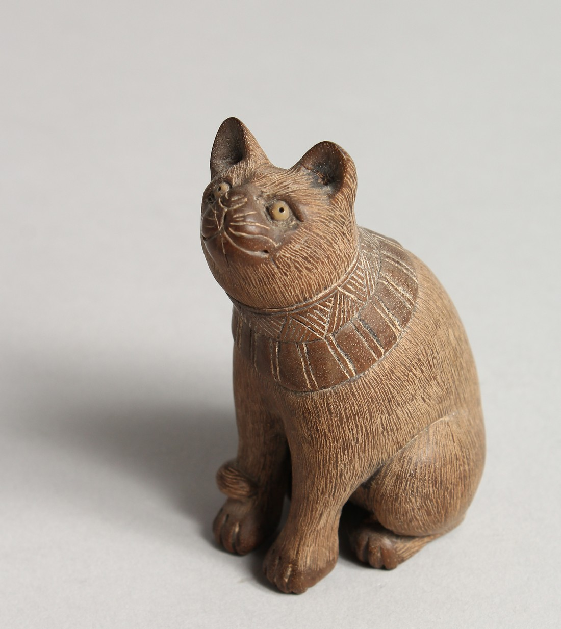 A JAPANESE CARVED WOODEN SEATED CAT Signed