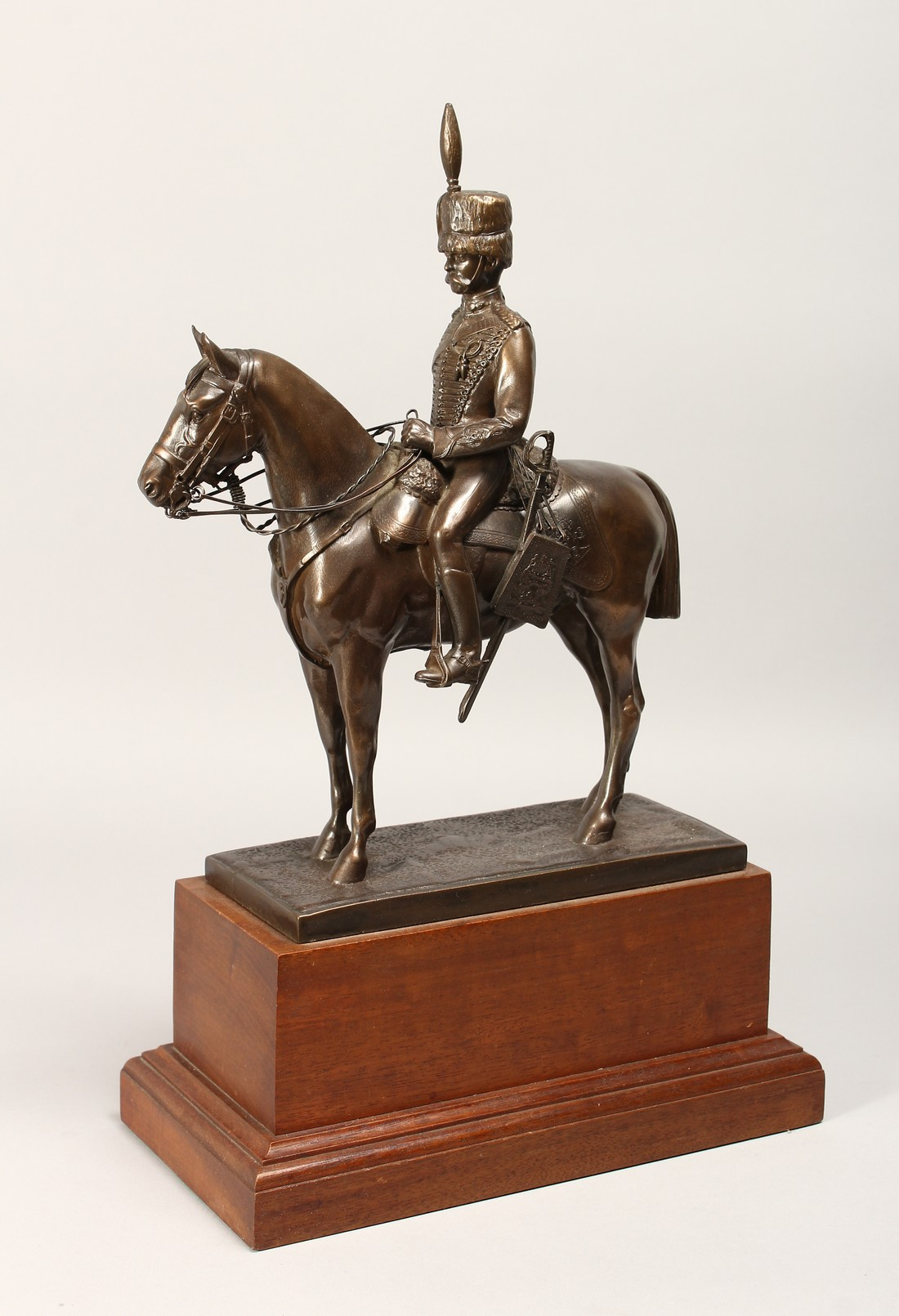 A BRONZE OVERLAID COMPOSITE MODEL OF A HUSSAR ON HORSEBACK, on a wooden plinth base 17ins high.