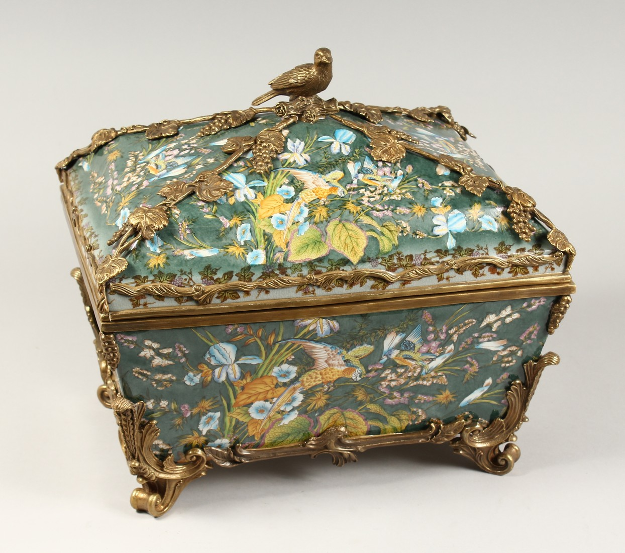 A LARGE CONTINENTAL STYLE PORCELAIN AND BRONZE MOUNTED CASKET, decorated with exotic flowers and